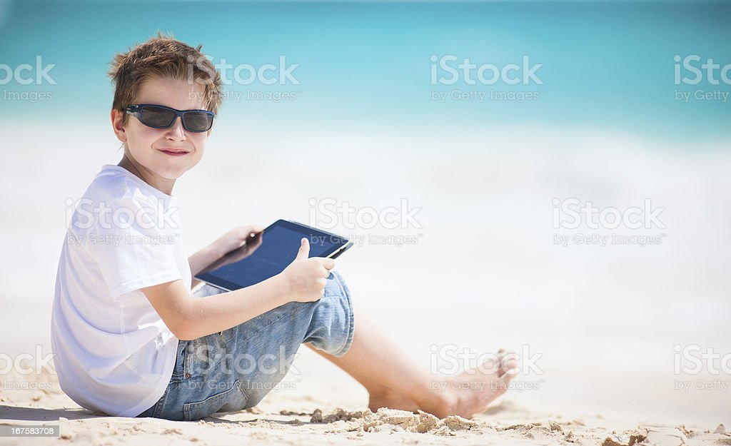 Boy with tablet device at beach royalty-free stock photo