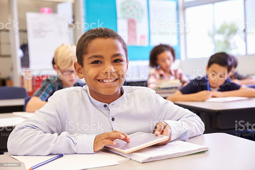 Boy with tablet in elementary school class, portrait stock photo