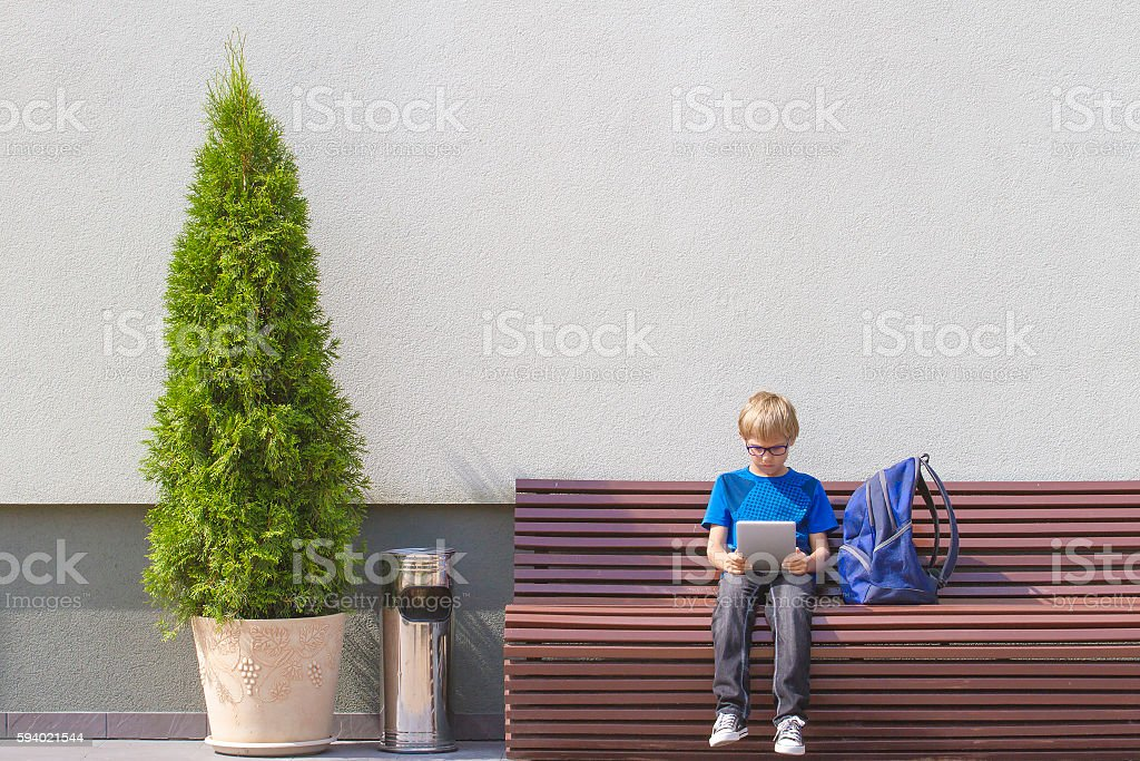 Boy with tablet PC and backpack sitting on the bench stock photo