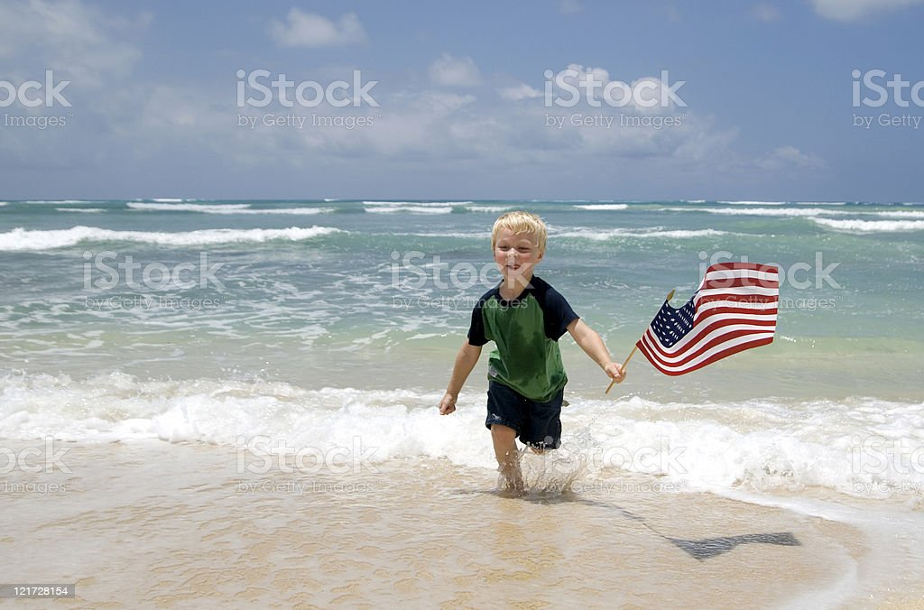 Boy with the American Flag on a Beach royalty-free stock photo
