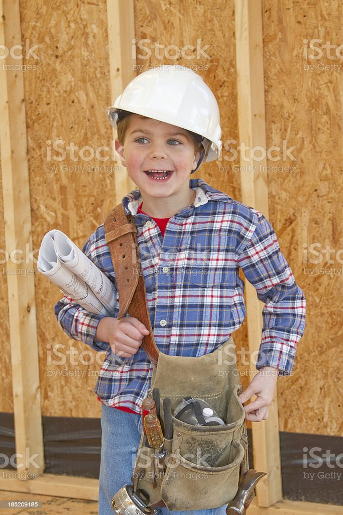 Boy With Tool Belt & Hardhat Standing In New Home Construction stock photo