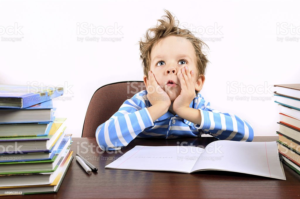 boy with tousled hair sitting at a desk royalty-free stock photo