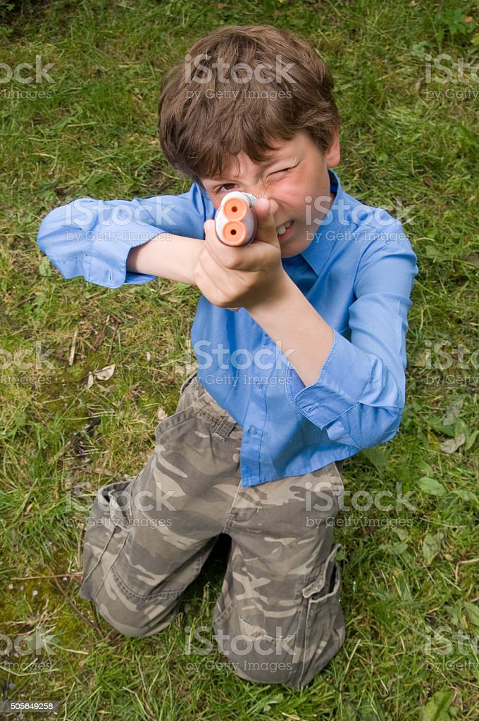 Boy with toy gun aiming at viewer stock photo