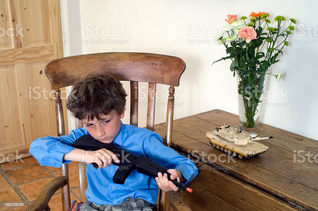 Boy with toy gun and tank stock photo