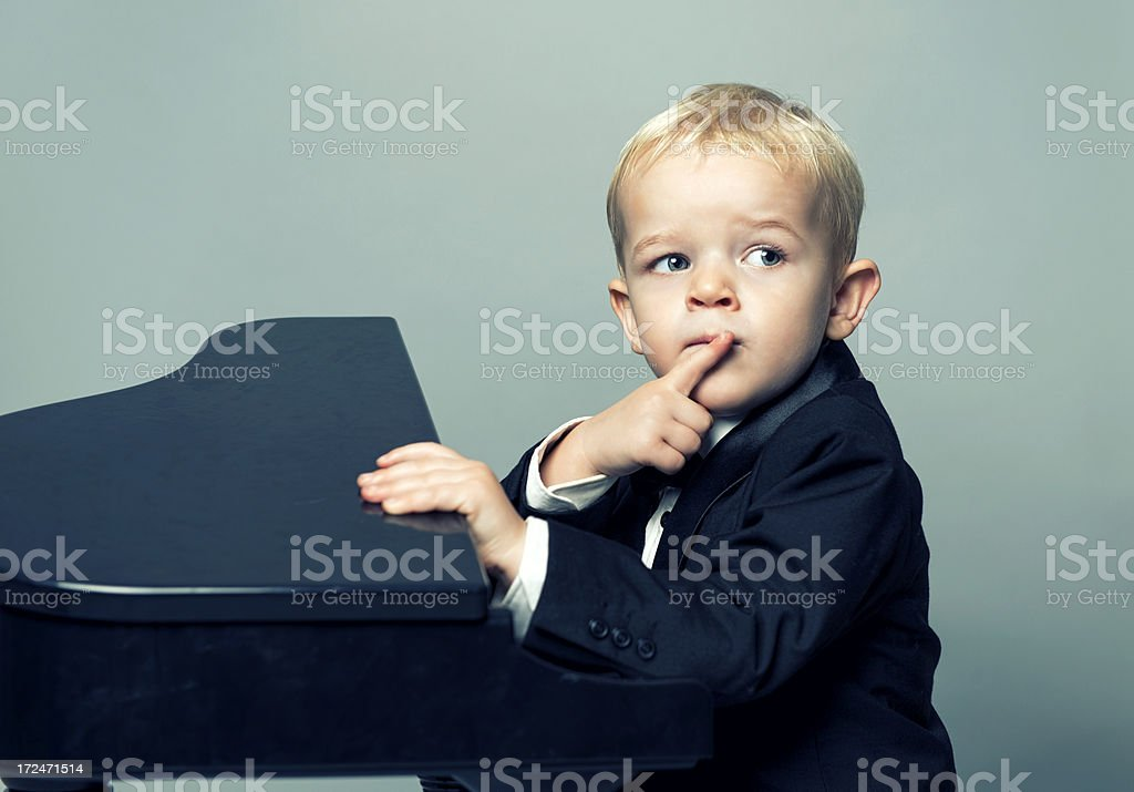 Boy with tuxedo sits in front of piano thinking royalty-free stock photo