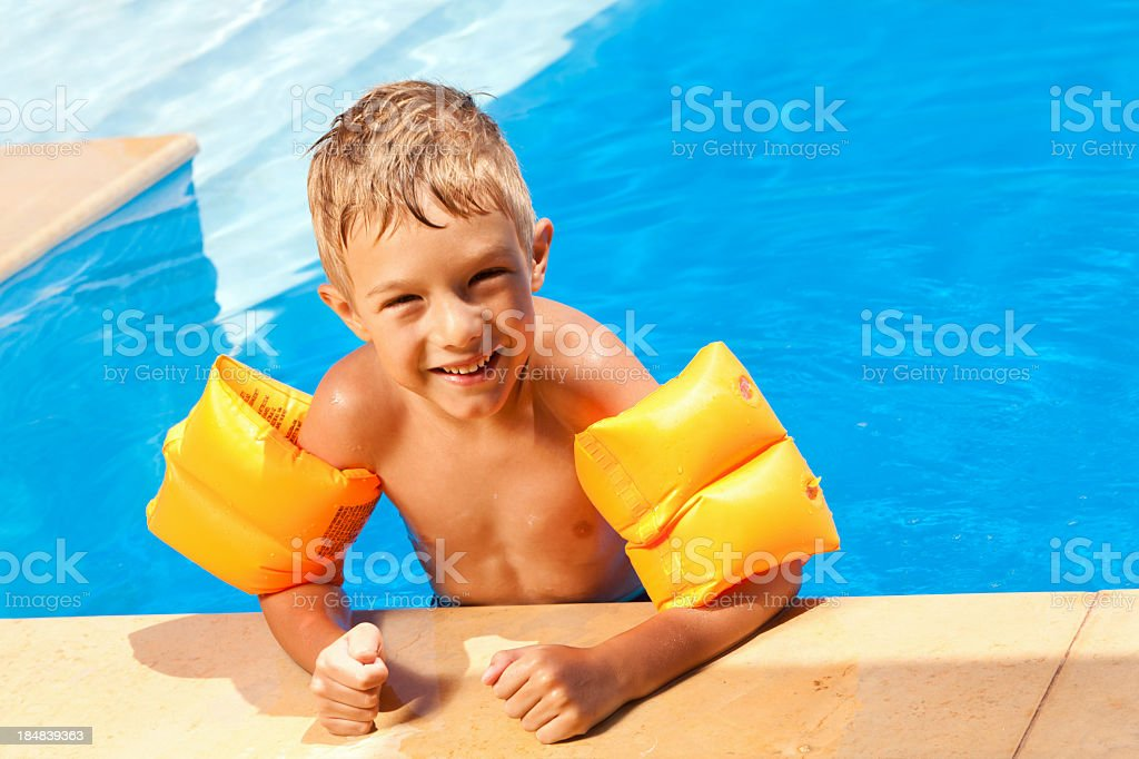 Boy with water wings in the swimming pool stock photo