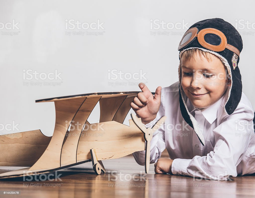 Boy with wooden plane model and a cap with cap stock photo