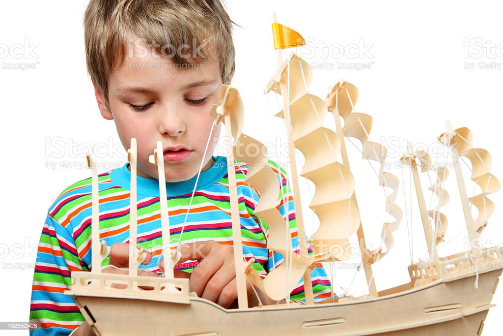 Boy work with zeal on artificial ship, he fixes sails royalty-free stock photo
