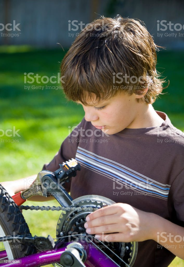 Boy Working on a Bicycle stock photo