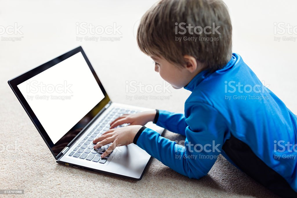 Boy working on laptop computer stock photo