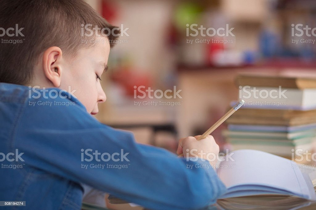 Boy writing his homework rear view stock photo