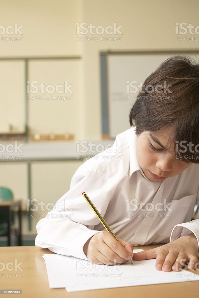 Boy writing in classroom royalty-free stock photo