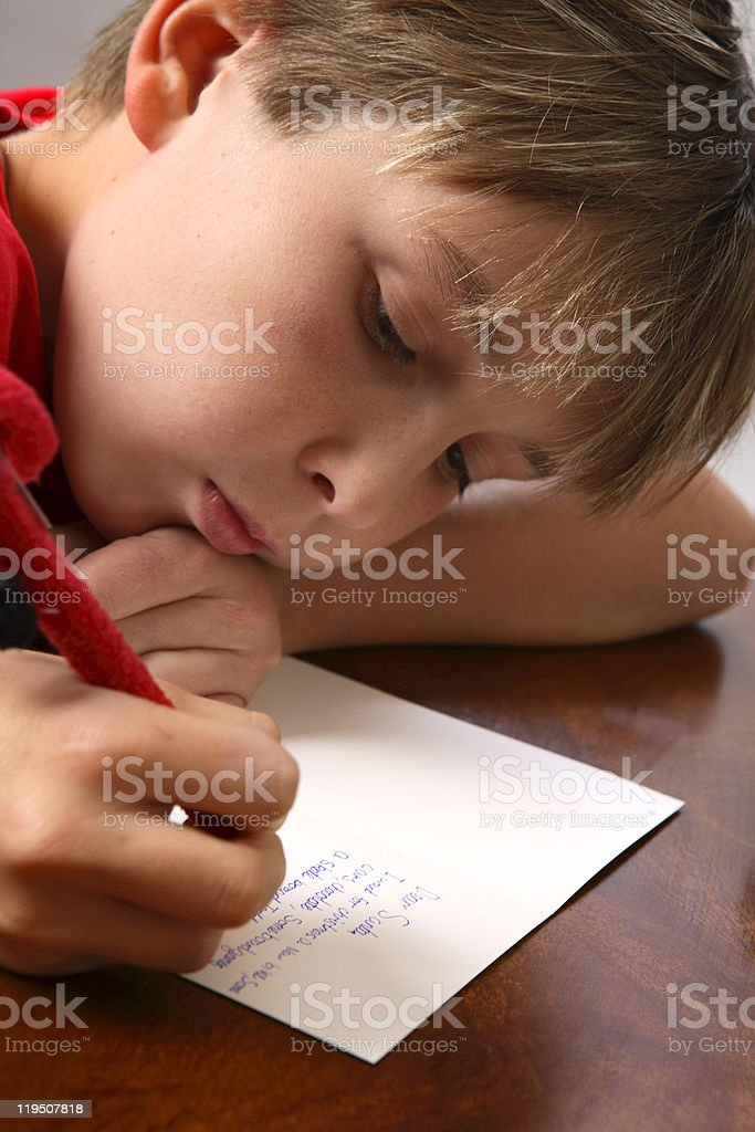 Boy writing note letter to santa royalty-free stock photo