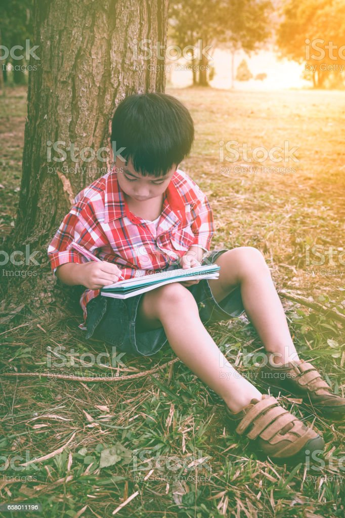 Boy writing on book. Education concept. Vintage style. stock photo