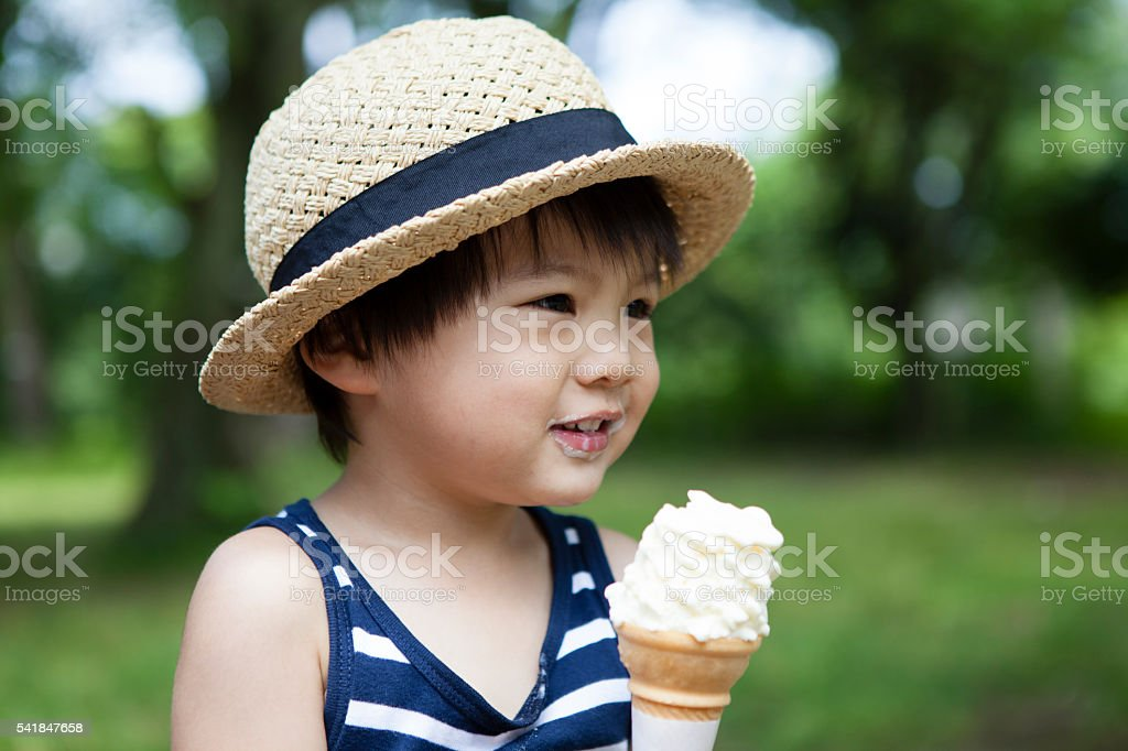 Boy you have a soft-serve ice cream in the park stock photo