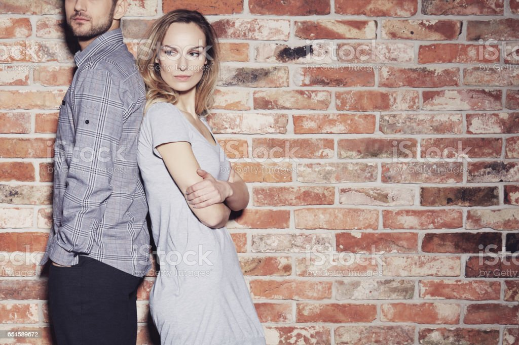 Boyfriend and girlfriend standing back to back stock photo