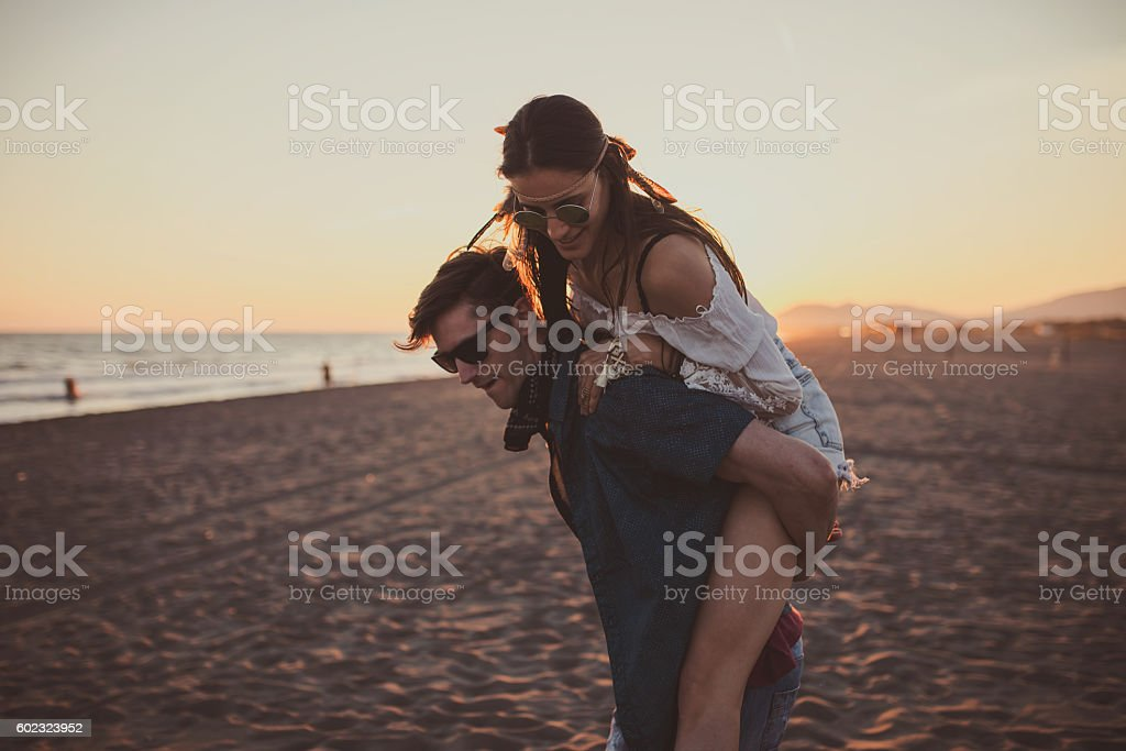 Boyfriend carrying his tired girlfriends on his back stock photo