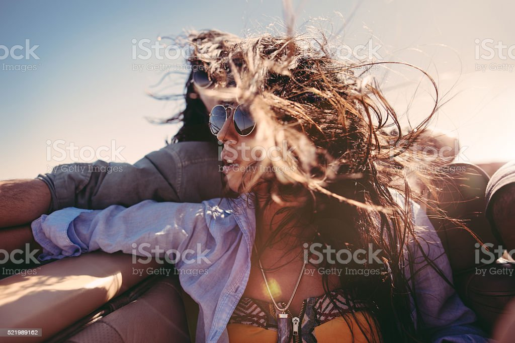 Boyfriend embracing girl on back seat of a convertible car stock photo