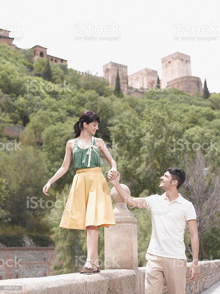 Boyfriend helping girlfriend balance on stone wall royalty-free stock photo