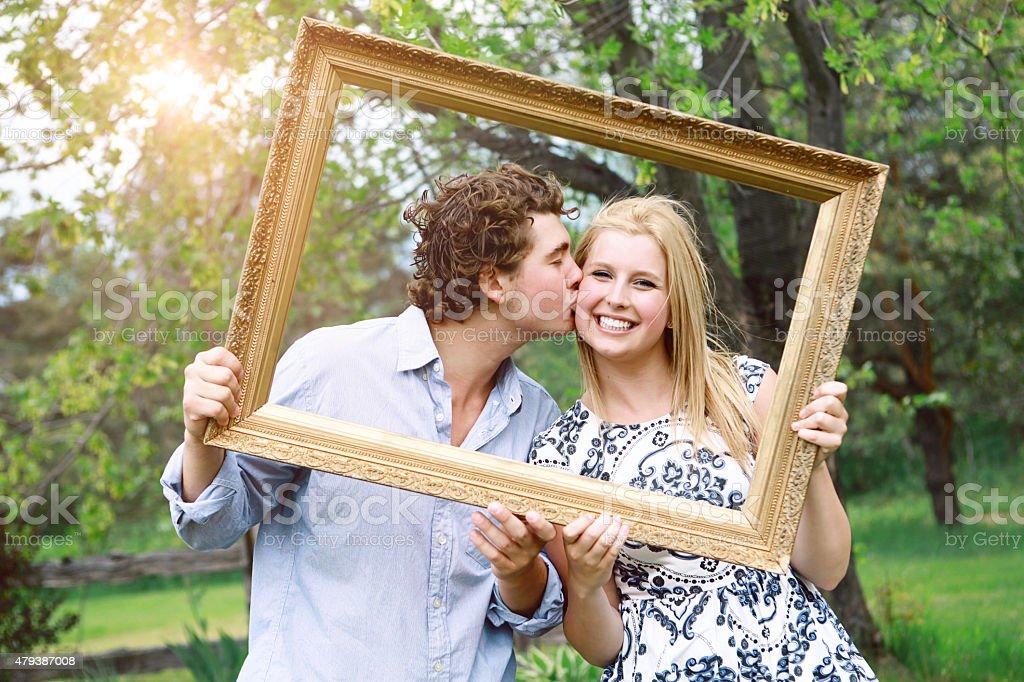 Boyfriend Kissing His Girlfriend as They Peek Through  Picture Frame stock photo