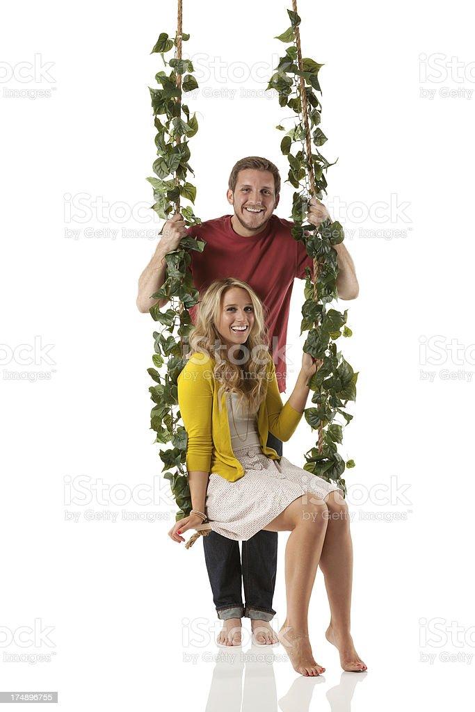 Boyfriend pushing his girlfriend on a swing royalty-free stock photo
