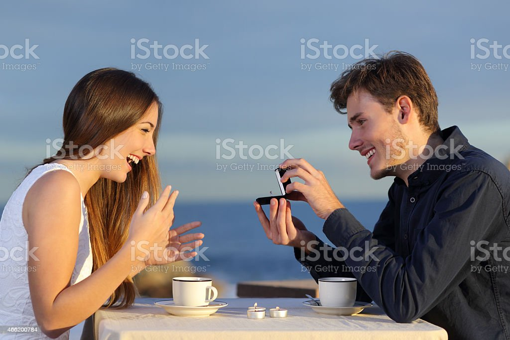 Boyfriend requesting hand of his girlfriend with a engagement ring stock photo