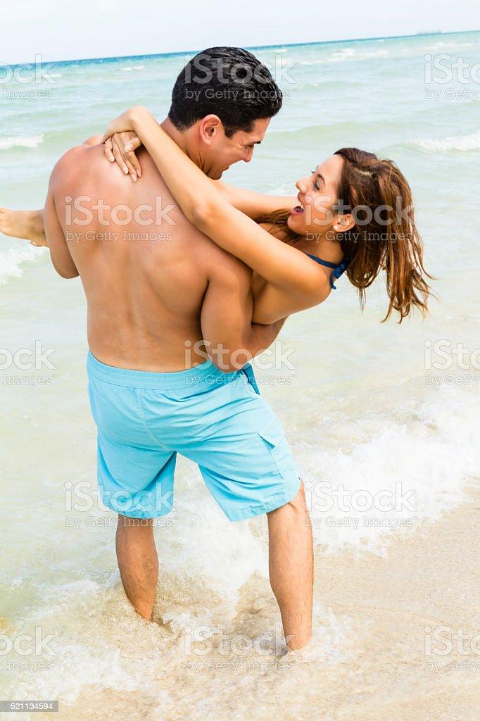 Boyfriend smiling and lifting happy girlfriend on beach stock photo