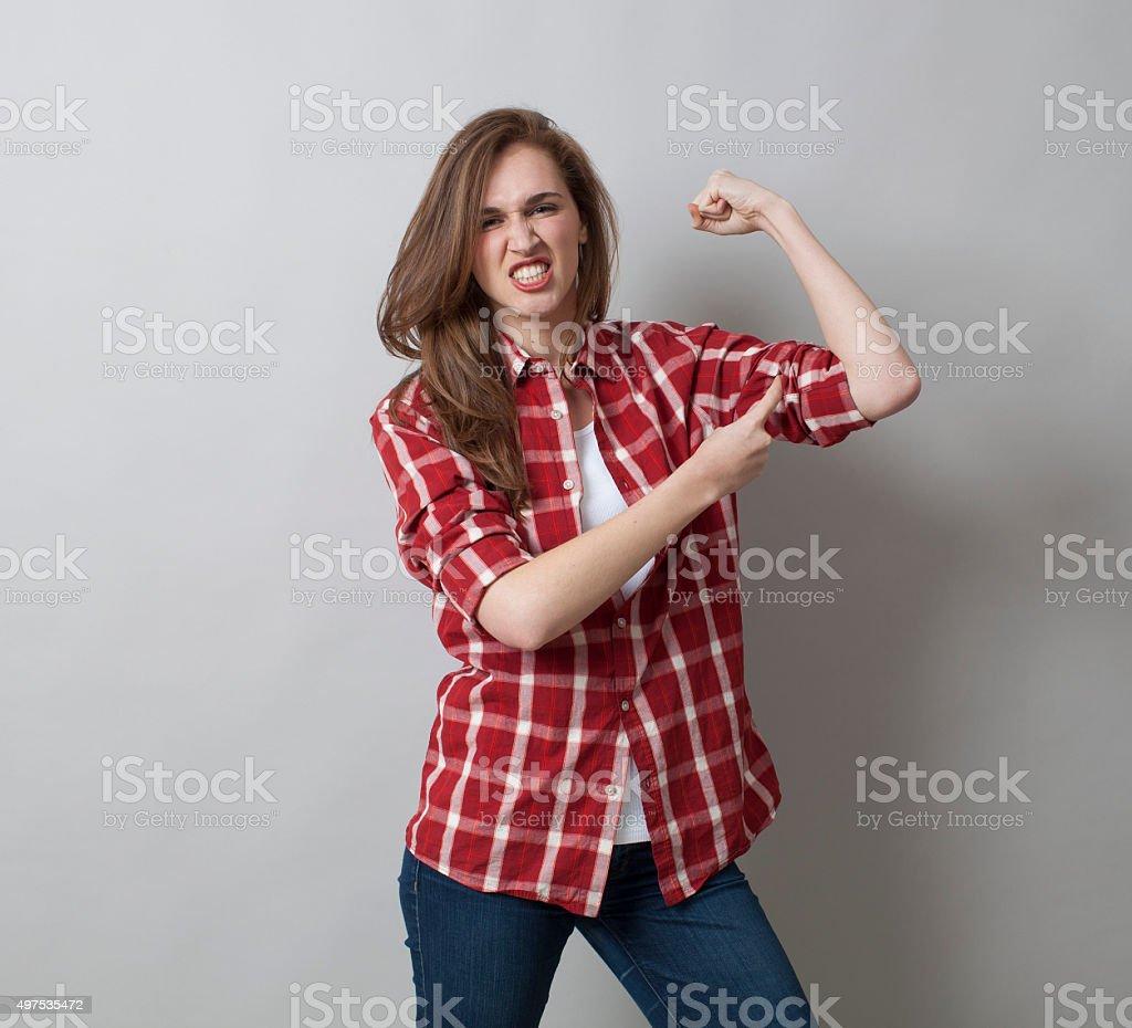 boyish 20s woman showing her muscular checked shirt stock photo