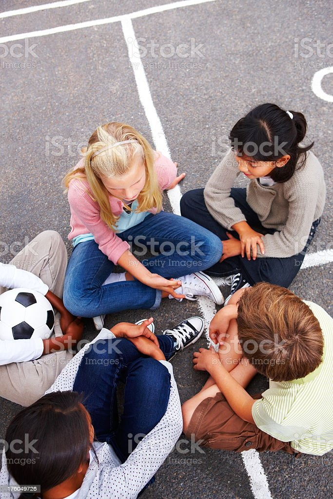 Boys and girls discussing while sitting on street royalty-free stock photo