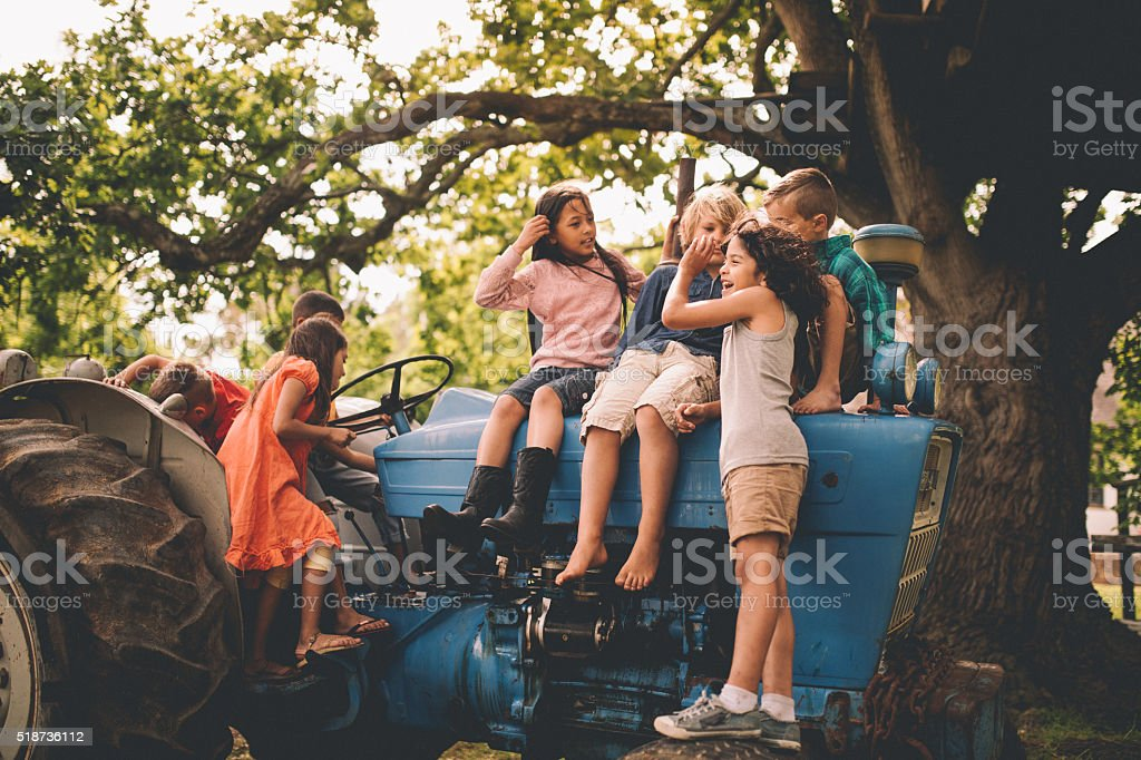 Boys and girls playing on an old tractor under tree stock photo