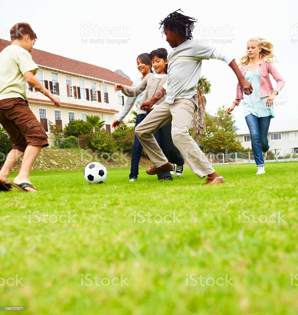 Boys and girls playing soccer in park with building behind royalty-free stock photo