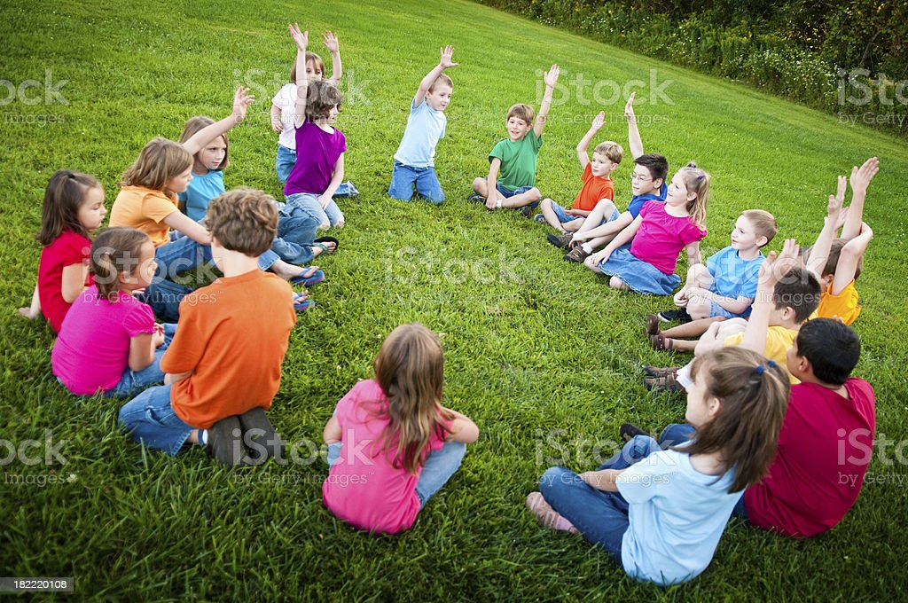Boys and Girls Sitting in a Circle Raising Hands royalty-free stock photo
