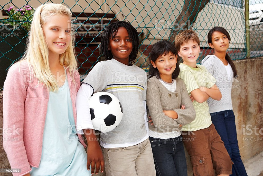 Boys and girls standing with a football royalty-free stock photo