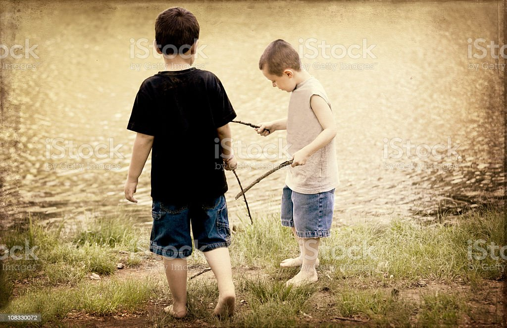 Boys and their sticks in the park stock photo