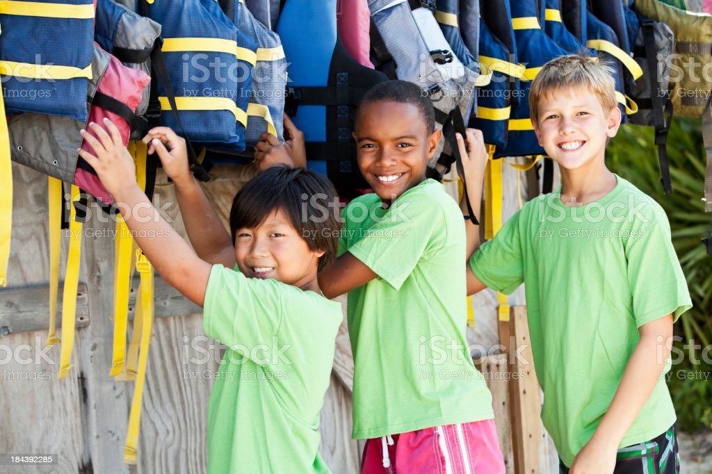 Boys at water sports equipment shack reaching for life jackets royalty-free stock photo