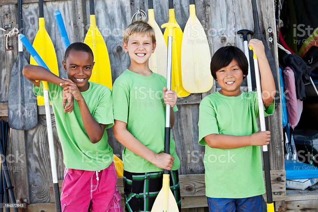 Boys at water sports equipment shack with paddles stock photo