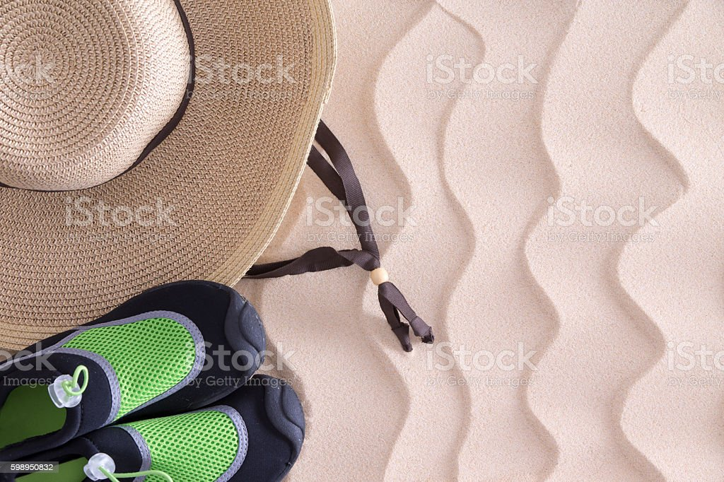 Boys beach hat and shoes on golden sand stock photo