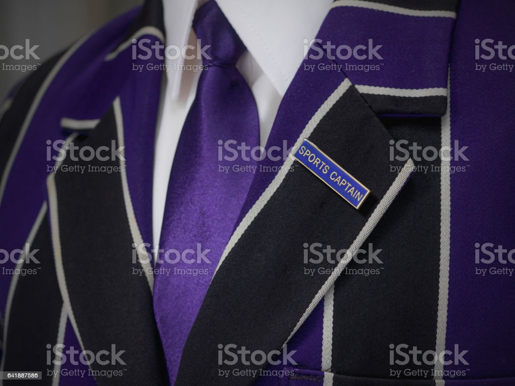 Boys blazer with school blue sports captain badge stock photo