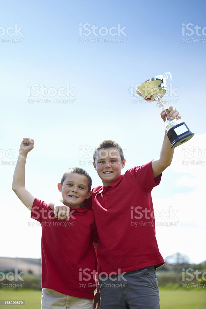 Boys cheering with trophy outdoors stock photo