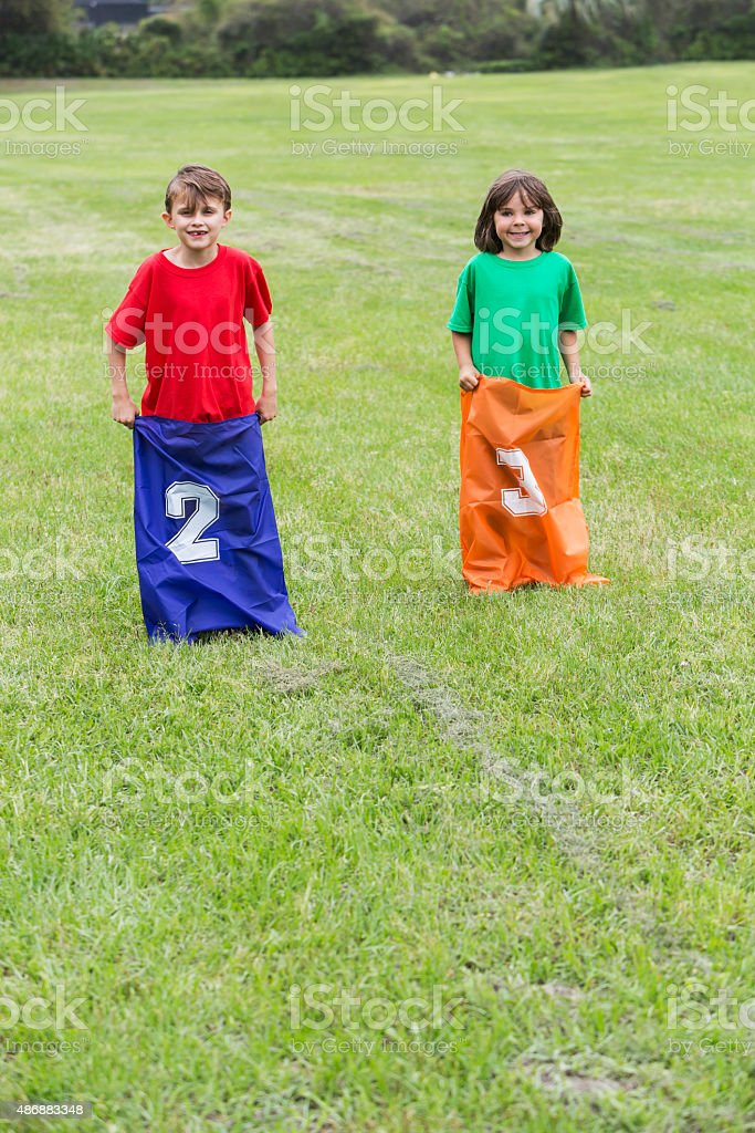Boys competing in a potato sack race stock photo