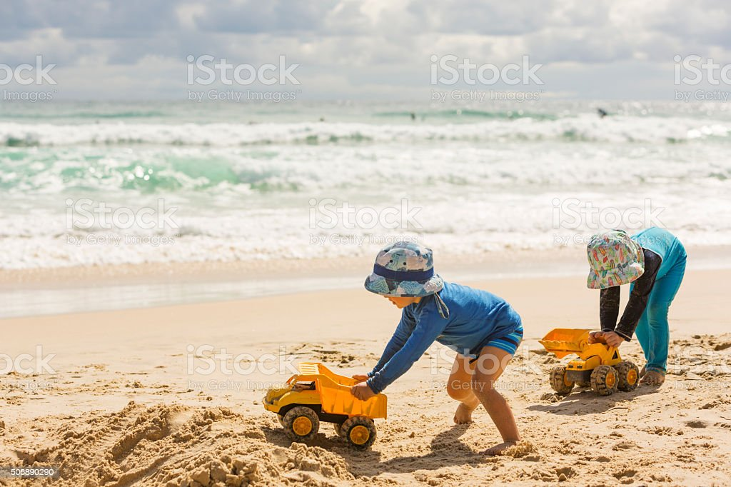 Boys Digging in The Sand at the Beach stock photo