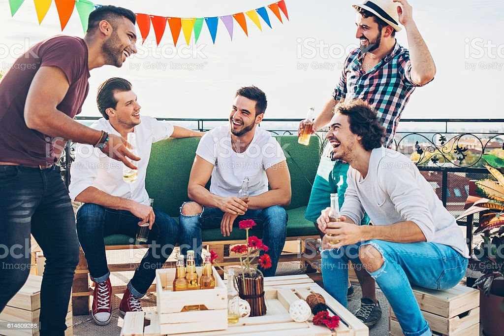 Boys drinking beer on the rooftop stock photo