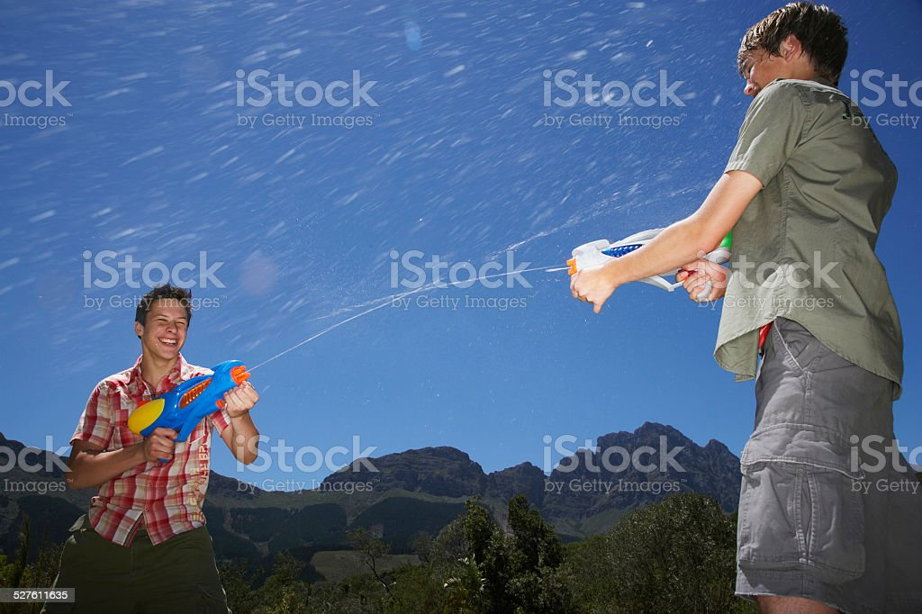 Boys Fighting With Water Guns In Mountains stock photo