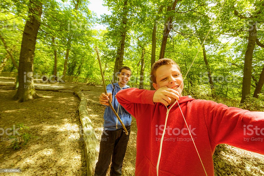 boys firing bows in the wood stock photo