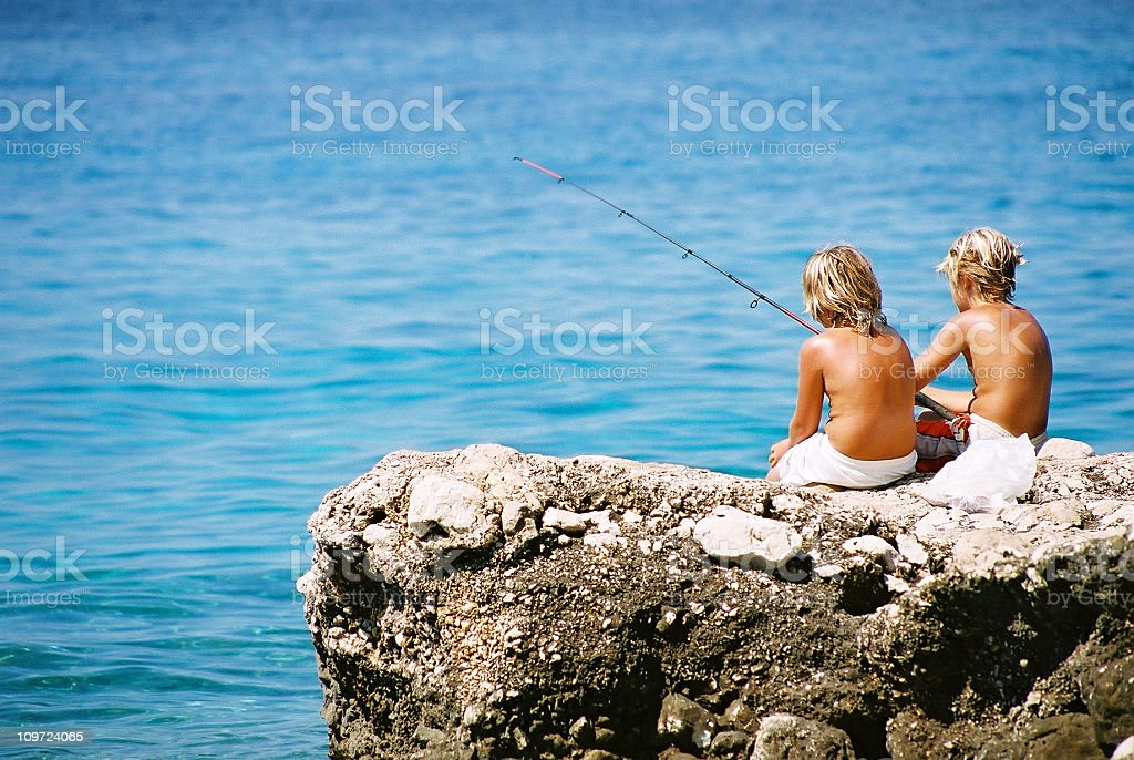 Boys fishing on the beach royalty-free stock photo