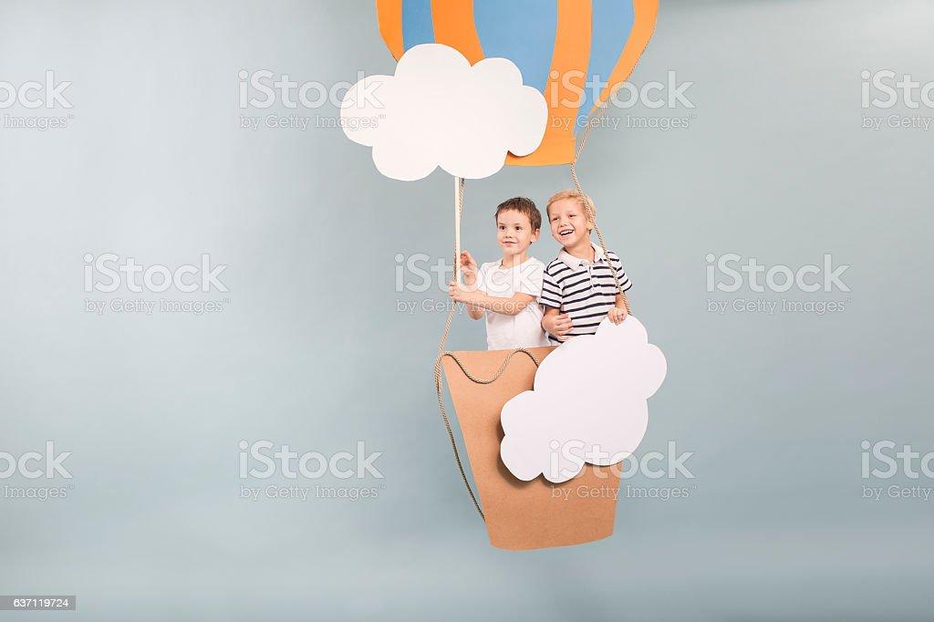 Boys flying in baloon stock photo