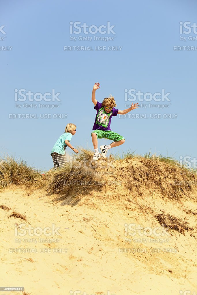 boys having fun jumping together in sand dunes royalty-free stock photo