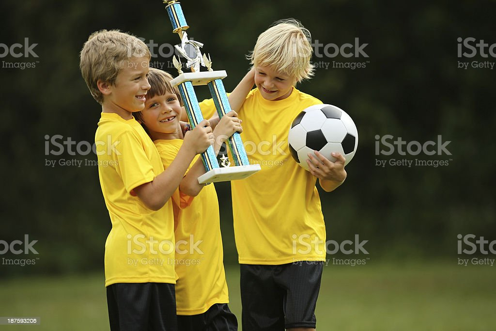 Boys Holding Soccer Trophy On Playing Field royalty-free stock photo