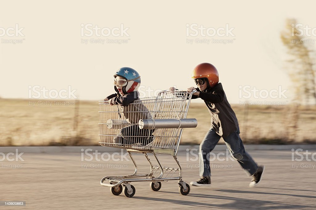 Boys in Helmets Race a Shopping Cart stock photo