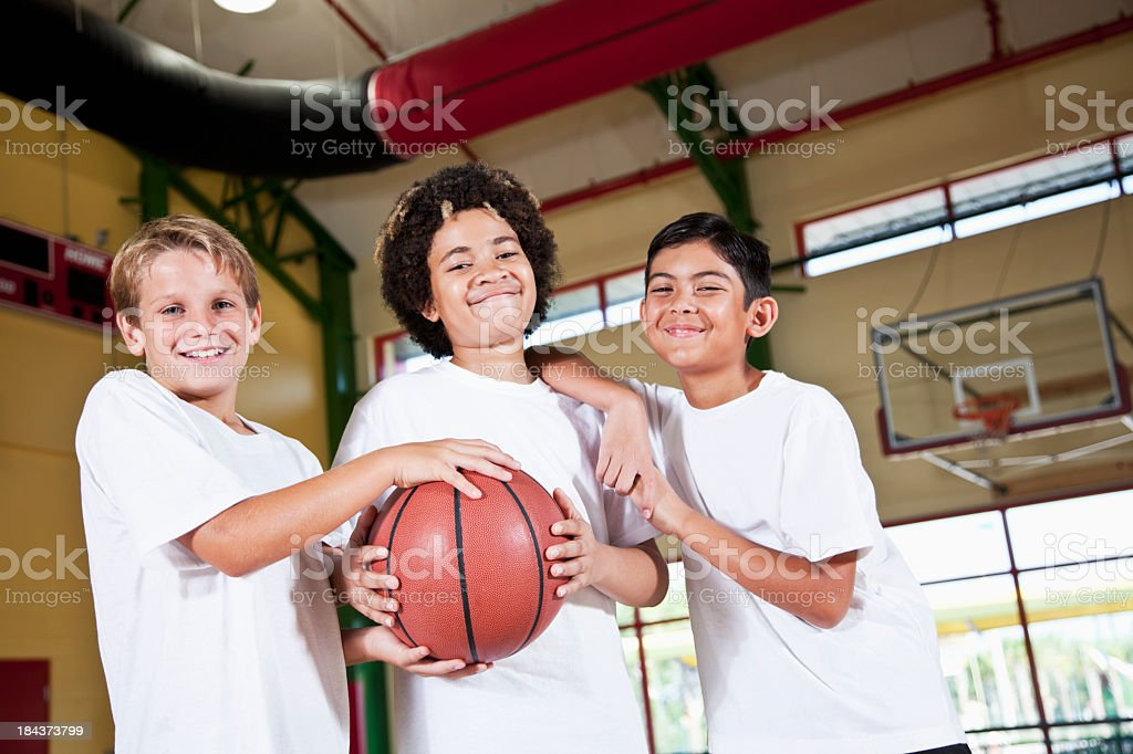 Boys in school gymnasium holding basketball stock photo